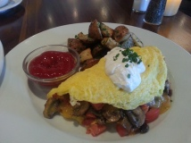 Applewood Smoked Bacon Omelet with 3 eggs, bacon, mushrooms, tomato, cheddar, and sour cream